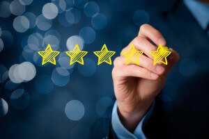 Review increase rating or ranking evaluation and classification concept. Businessman draw five yellow star to increase rating of his company. Bokeh in background.